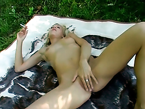 Rubbing her juicy wet pussy while smoking a cigarette.