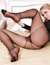 Blonde Julie posing on bed in her black pantyhose