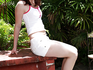 Stunning brunette gets ready to play with herself outdoors